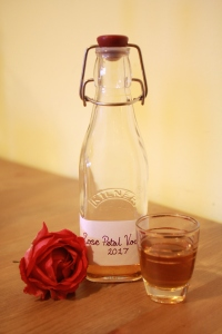 Bottle of rose petal vodka shot glass and rose